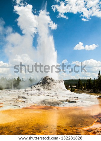 Castle Geyser, in Yellowstone National Park's Upper Geyser Basin, erupts with a colorful thermal pool in the foreground. - stock photo