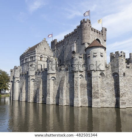 castle Gravensteen in the Beldian city of Ghent with reflection in in river and blue sky