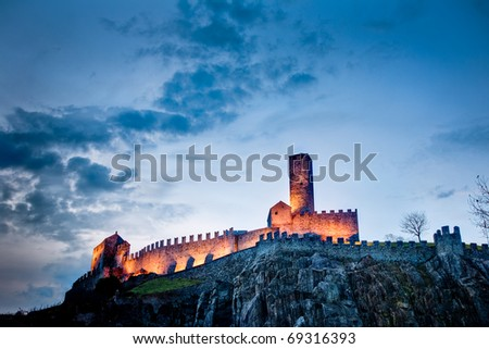 castle in twilight lit by artificial lights, Bellinzona - stock photo