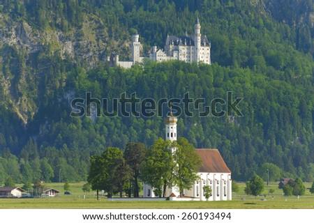 castle Neuschwanstein and pilgrimage church St. Coloman in Bavaria - stock photo