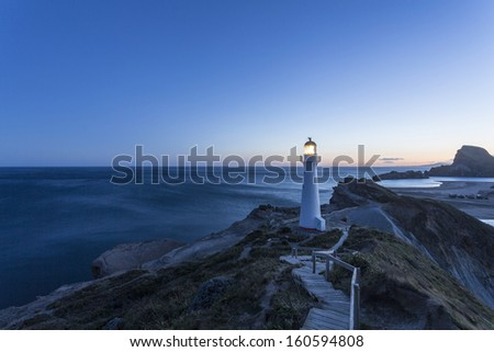 Castle Point Lighthouse/ the lighthouse at Castlepoint, Wairarapa New Zealand, shot at dusk as the lighthouse light comes on - stock photo