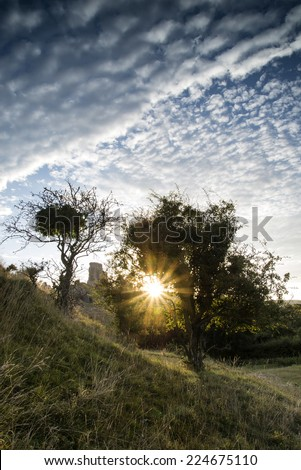Castle ruins landscape at sunrise with sunburst behind castle - stock photo
