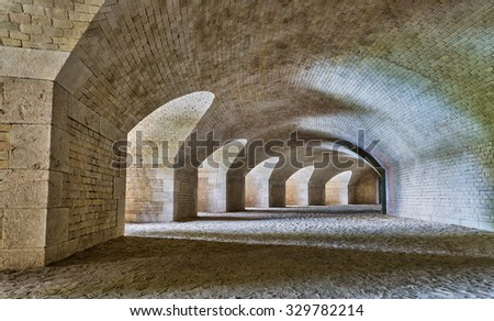 Castle tunnel interior with a series of arches in a ruined bastion fortress. - stock photo