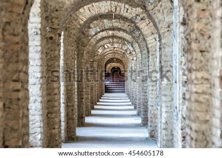 Castle tunnel with a series of arches and stair in the ruined Bastion fortress in the Slovak city of Komarno. - stock photo