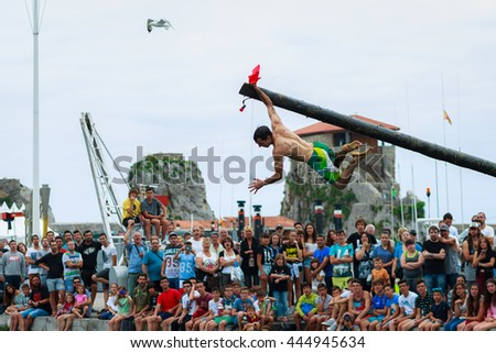 CASTRO URDIALES, SPAIN - JUNE 29: Unidentified boy holding the flag in the competition of the greasy pole celebrated in June 29, 2016 in Castro Urdiales, Spain