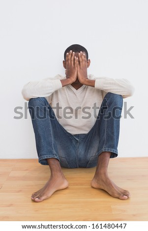 Casual Afro young man sitting against wall with hands covering face