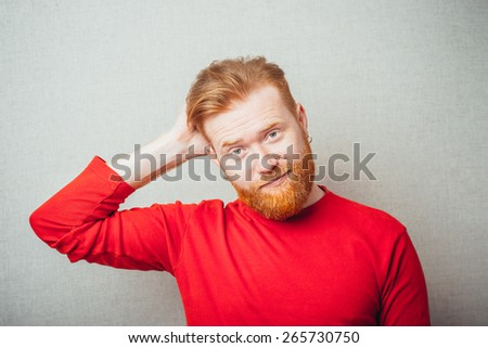 Casual and cool. Young hipster red bearded Man holding hand on head while standing against stripped background - stock photo