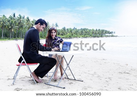 Casual Asian business people having a meeting on the beach - stock photo