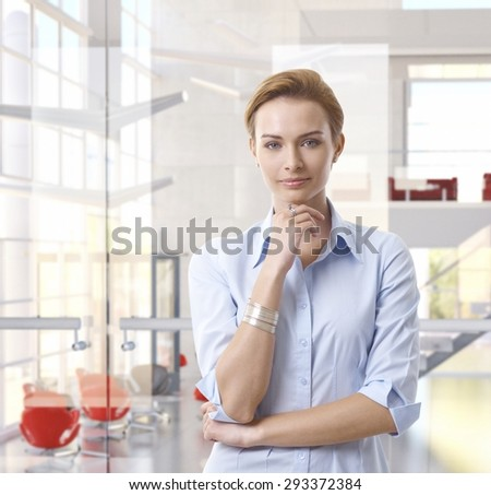 Casual attractive caucasian businesswoman standing at classy bright business office, looking at camera, hand under chin, copyspace. - stock photo