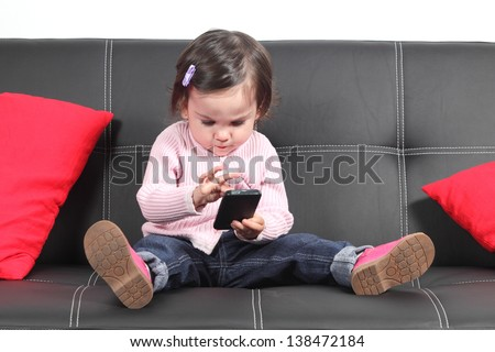 Casual baby sitting on a couch at home playing and touching a mobile phone - stock photo