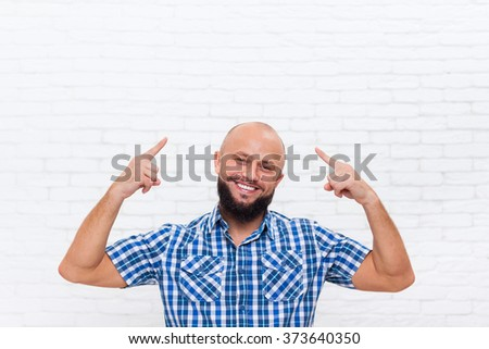 Casual Bald Bearded Business Man Smiling Point Fingers Up Head Office White Brick Wall - stock photo