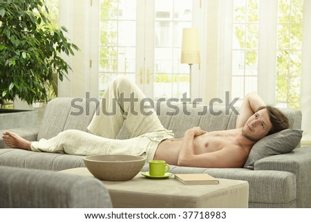 Casual bare chested young man resting on couch at home. - stock photo