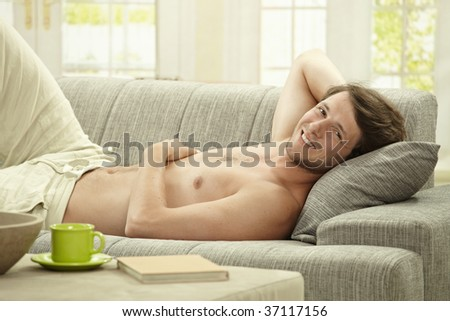 Casual bare chested young man resting on couch at home, smiling.