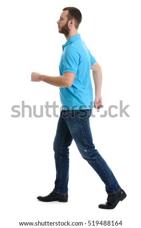 casual bearded man wearing polo and jeans walking over white background