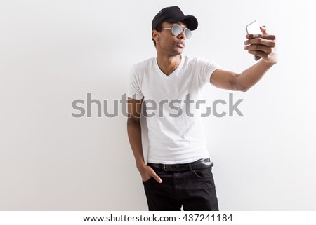 Casual black guy in shades and cap taking selfie with smart phone on light background with copy space - stock photo