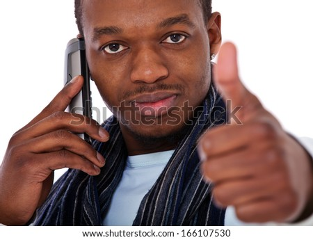 Casual black guy showing thumbs up while talking on the phone. All on white background.