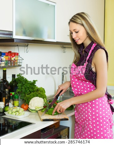 Casual blonde girl slicing green pepper at table at domestic kitchen