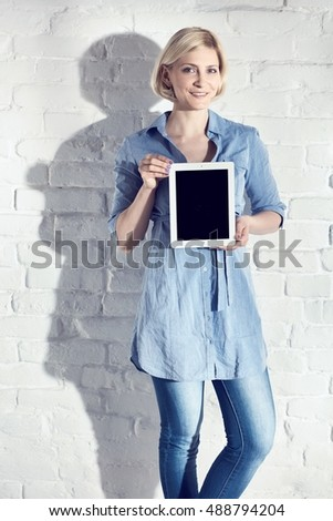 Casual blonde woman holding tablet computer with blank screen, smiling, looking at camera.