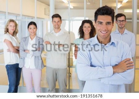 Casual boss smiling at camera in front of business team in the office