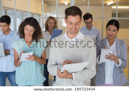 Casual boss standing in front of his team all taking notes in the office