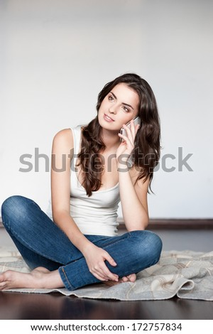 casual brunette young woman in white singlet and jeans sitting on wool plaid and talking on cell phone - stock photo