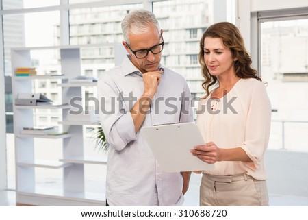 Casual business colleagues looking at clipboard in the office - stock photo