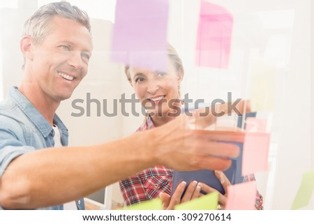 Casual business colleagues reading sticky notes in the office - stock photo