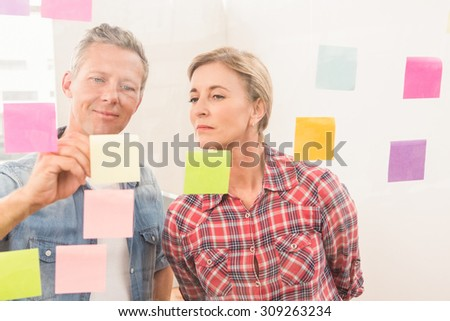 Casual business colleagues writing on sticky notes in the office - stock photo