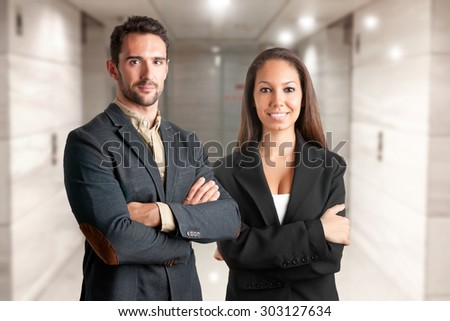 Casual business man and woman with arms crossed  - stock photo