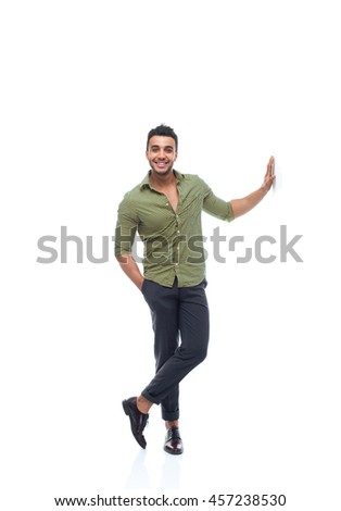 Casual business man happy smile young handsome guy hand on wall full length wear shirt isolated white background - stock photo
