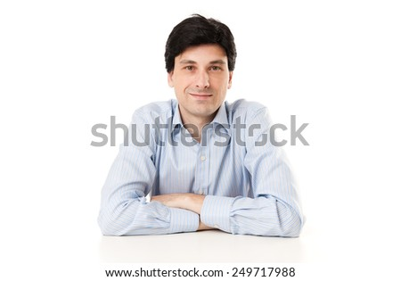 casual business man sitting at a desk and looking and camera - stock photo