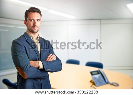 Casual business man with arms crossed in a meeting room - stock photo