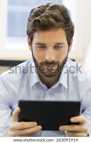 Casual business man working on tablet computer in office - stock photo