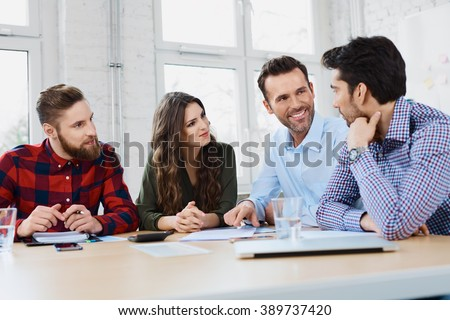 Casual business partners talking during business meeting in office. - stock photo