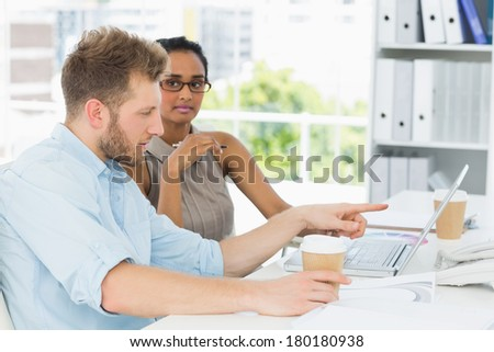 Casual business partners working together on laptop at desk in creative office
