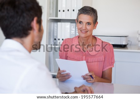 Casual business people having a meeting at desk in her office