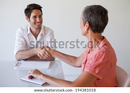 Casual business people shaking hands at desk and smiling in the office - stock photo