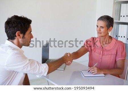 Casual business people shaking hands at desk in her office