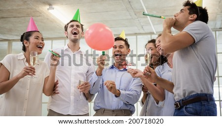 Casual business team celebrating with champagne and party horns in the office - stock photo
