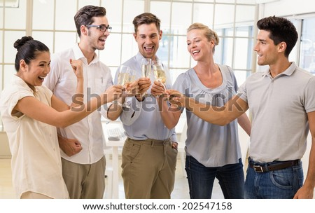 Casual business team celebrating with champagne in the office - stock photo