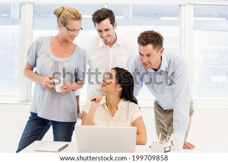 Casual business team having a meeting using laptop in the office - stock photo