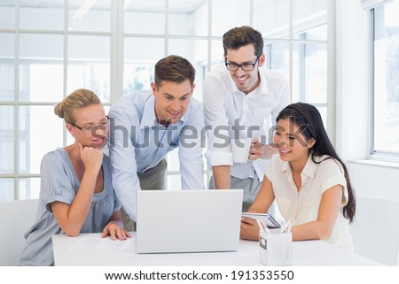 Casual business team looking at laptop together in the office - stock photo