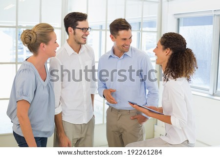 Casual business team smiling and talking in the office - stock photo