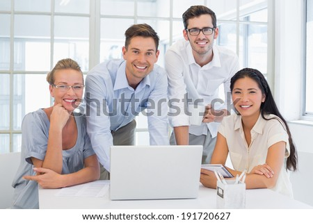 Casual business team smiling at camera together at desk in the office