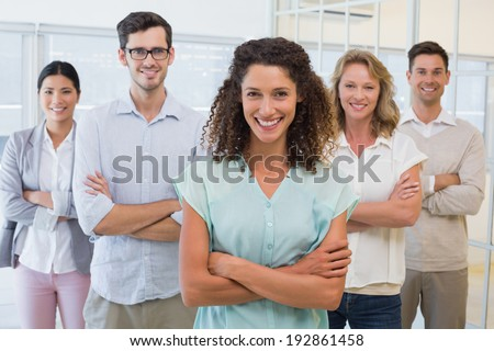 Casual business team smiling at camera with arms crossed in the office - stock photo