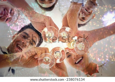 Casual business team toasting with champagne against colourful fireworks exploding on black background - stock photo