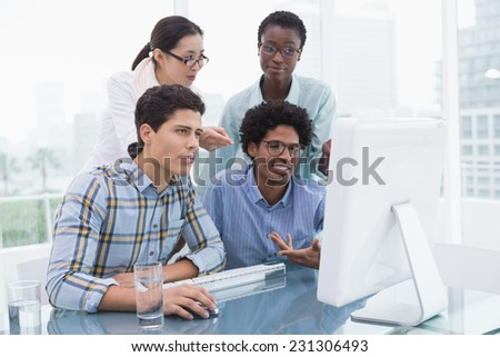 Casual business team working together at desk in creative office