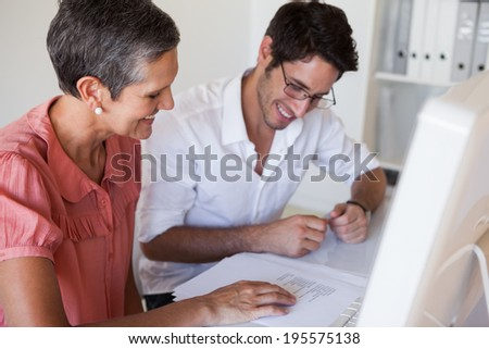 Casual business team working together at desk using computer in the office