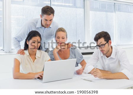 Casual business team working together at desk using laptop in the office