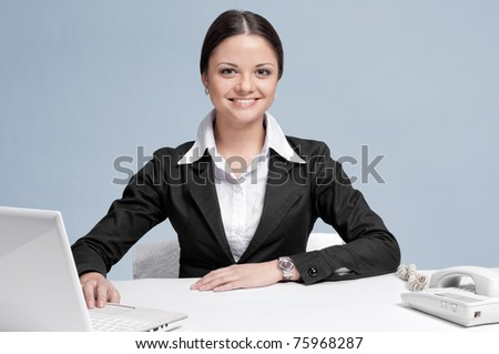 Casual business woman in office working with white table, laptop and phone. Smile.